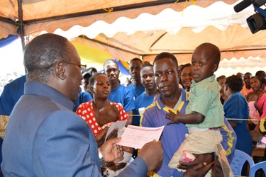 Minister for Constitutional Affairs, Dr Harrison Mwakyembe (L) presents a birth certificate to a parent