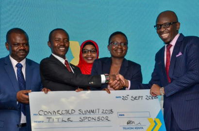 Telkom Kenya's Kris Senanu hands a dummy cheque to Kenya's ICT CS Joe Mucheru