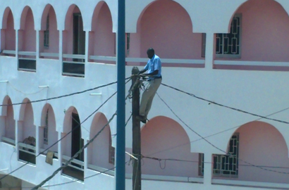 A technician repairs cables that fell from a pole in a street in Dakar, Senegal